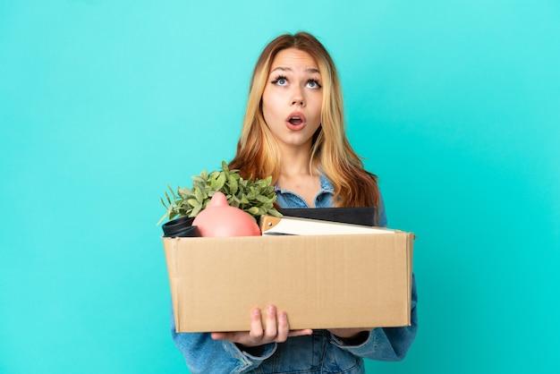 Блондинка-подросток делает движение, поднимая коробку, полную вещей, глядя вверх и с удивленным выражением лица