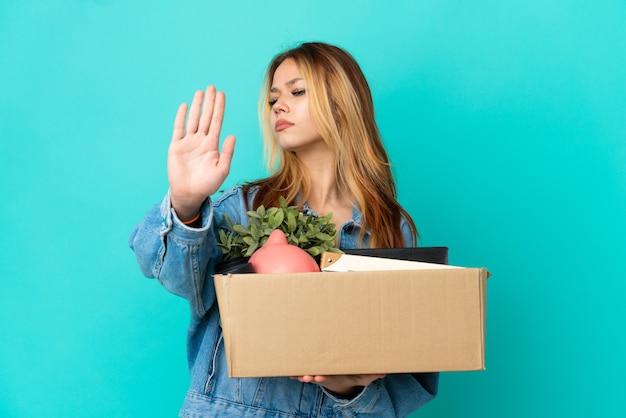 Блондинка-подросток делает движение, поднимая коробку, полную вещей, делая стоп-жест и разочарованная