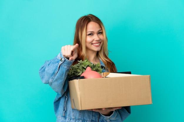 Блондинка-подросток делает движение, поднимая коробку, полную вещей, указывая вперед со счастливым выражением лица