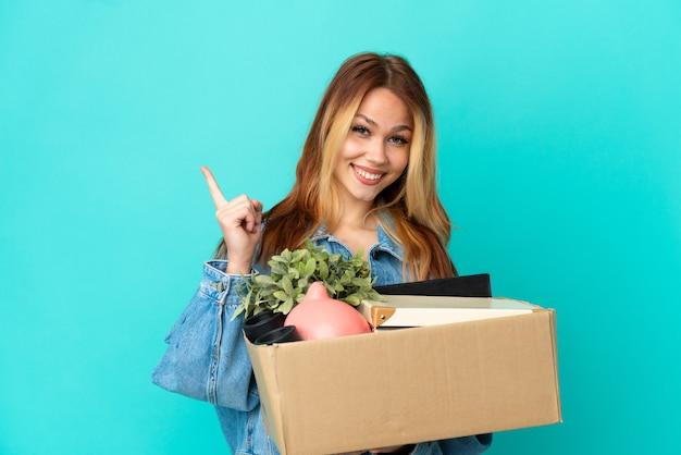 Блондинка-подросток делает движение, поднимая коробку, полную вещей, указывая в сторону, чтобы представить продукт