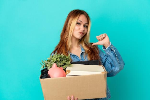 Блондинка-подросток делает движение, поднимая коробку, полную вещей, гордых и самодовольных