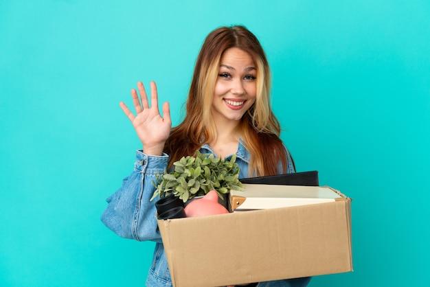 Блондинка-подросток делает движение, поднимая коробку, полную вещей, салютуя рукой со счастливым выражением лица