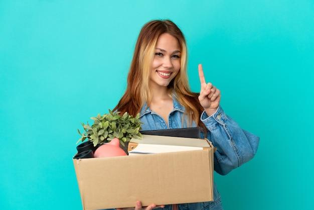 Блондинка-подросток делает движение, поднимая коробку, полную вещей, показывая и поднимая палец в знак лучшего