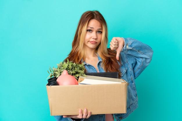 Блондинка-подросток делает движение, поднимая коробку, полную вещей, показывая большой палец вниз с отрицательным выражением лица