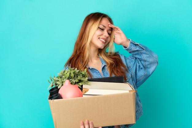 Блондинка-подросток делает движение, поднимая коробку, полную вещей, много улыбаясь
