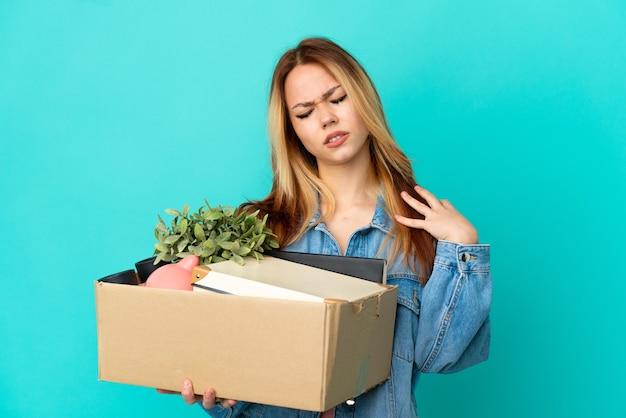 努力したことで肩の痛みに苦しんでいるものでいっぱいの箱を拾いながら動きをしている10代のブロンドの女の子