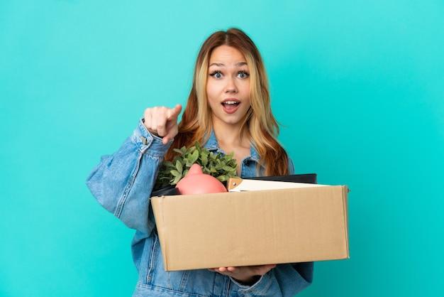 Блондинка-подросток делает движение, поднимая коробку, полную вещей, удивленную и указывая вперед