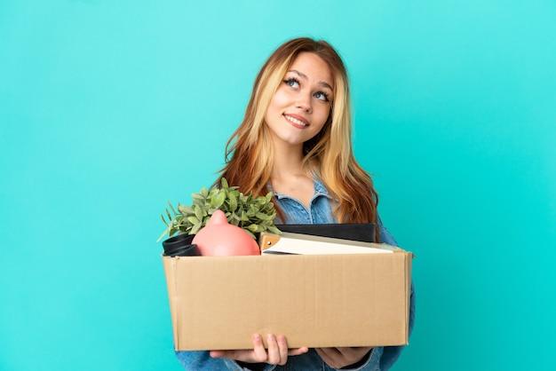 Блондинка-подросток делает движение, поднимая коробку, полную вещей, думая об идее, глядя вверх