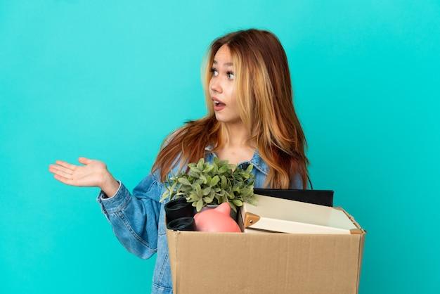 Блондинка-подросток делает движение, поднимая коробку, полную вещей, с удивленным выражением лица, глядя в сторону