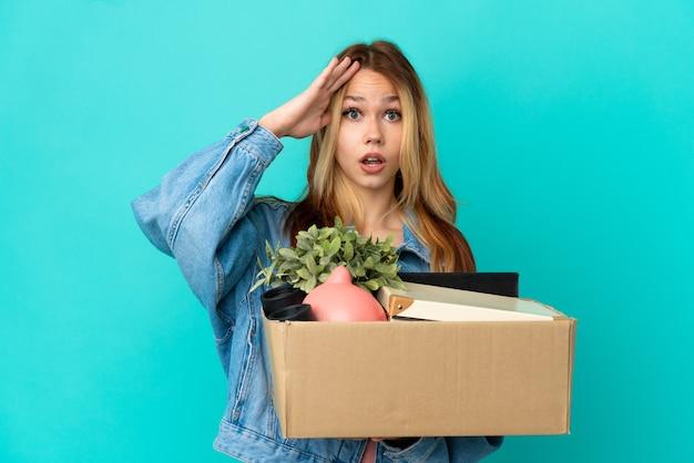 Блондинка-подросток делает движение, поднимая коробку, полную вещей, с удивленным выражением лица