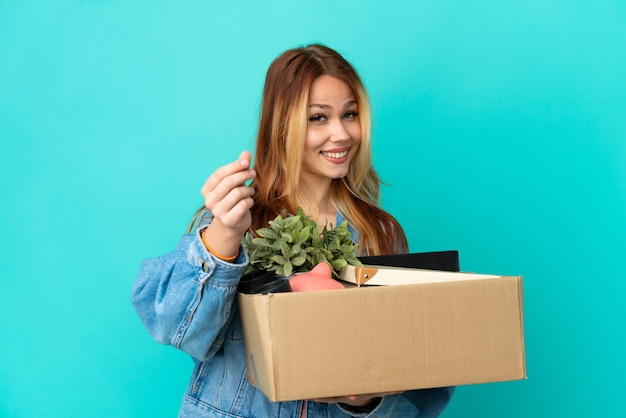 Teenager blonde girl making a move while picking up a box full of things making money gesture