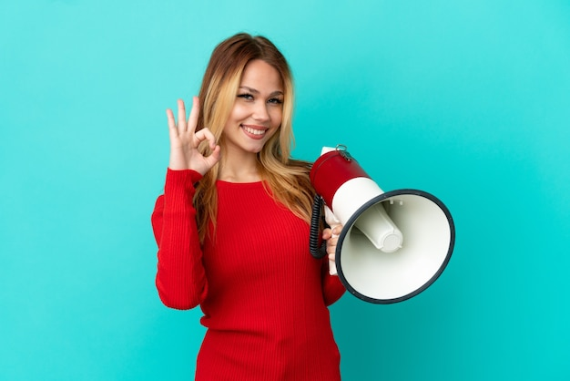 Девушка-подросток блондинка на изолированном синем фоне держит мегафон и показывает пальцами знак ок