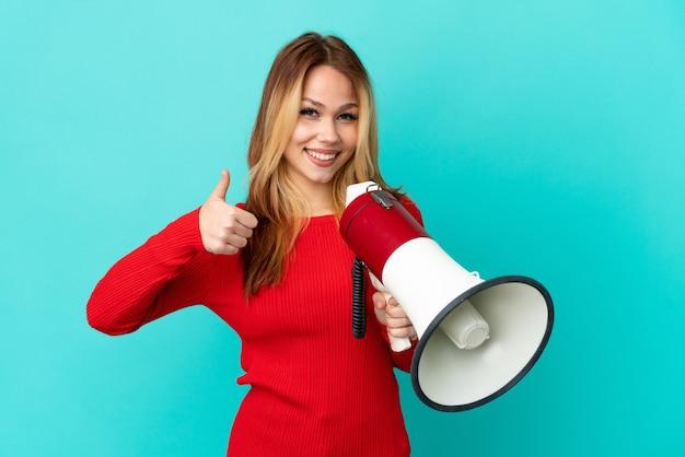 Блондинка девушка подросток на изолированном синем фоне держит мегафон большим пальцем вверх