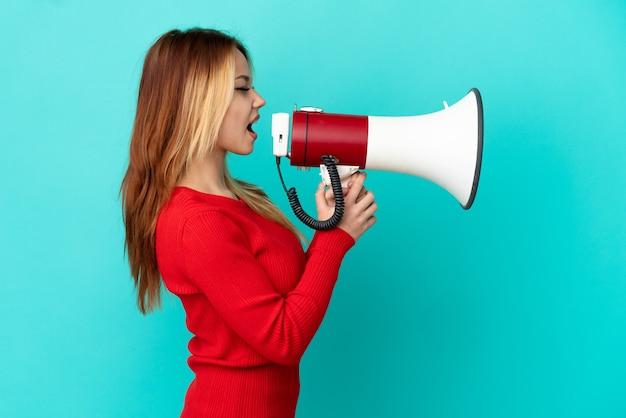 Блондинка-подросток на изолированном синем фоне кричит в мегафон, чтобы объявить что-то в боковом положении