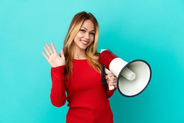 Девушка-подросток блондинка над изолированной синей стеной держит мегафон и салютует рукой со счастливым выражением лица