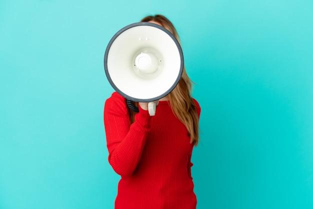 Блондинка-подросток над изолированной синей стеной кричит в мегафон, чтобы что-то объявить