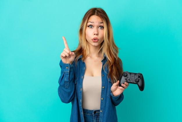 指を持ち上げながら解決策を実現しようとしている孤立した壁の上でビデオゲームコントローラーで遊んでいるティーンエイジャーのブロンドの女の子