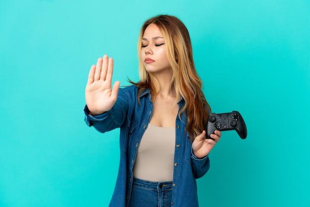 孤立した壁の上でビデオゲームコントローラーで遊んでいるティーンエイジャーのブロンドの女の子は、ジェスチャーを停止し、失望しました