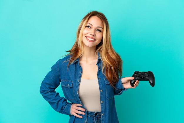 Блондинка-подросток играет с контроллером видеоигры над изолированной стеной, позирует с руками на бедрах и улыбается
