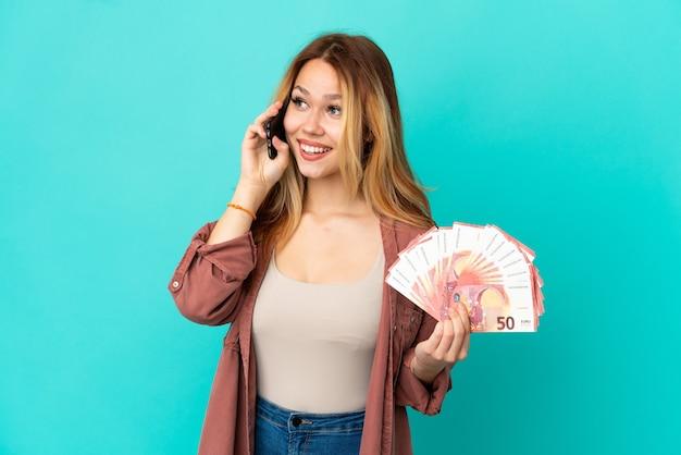 10대 금발 소녀는 고립된 파란색 배경 위에 많은 유로를 가지고 있으며 누군가와 휴대전화로 대화를 나누고 있다