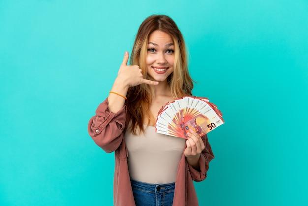 Девушка-подросток блондинка берет много евро на изолированном синем фоне, делая телефонный жест. перезвони мне знак