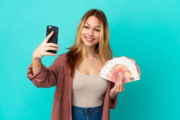 Teenager blonde girl taking a lot of euros over isolated blue background making a selfie