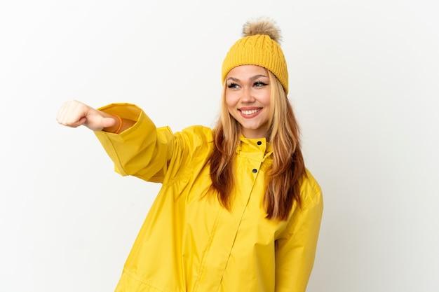 Блондинка девушка-подросток в непромокаемом пальто на изолированном белом фоне показывает жест рукой