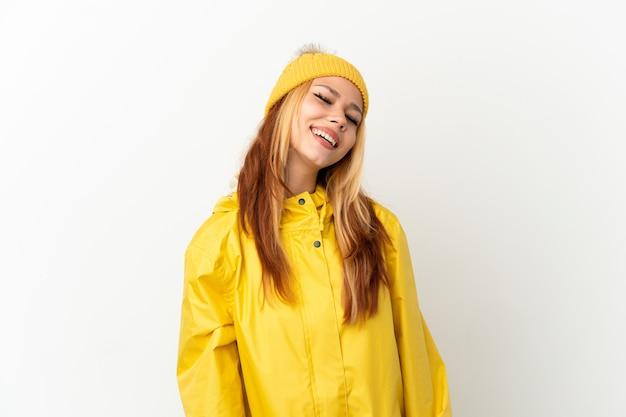 笑っている孤立した白い背景の上に防雨コートを着ているティーンエイジャーのブロンドの女の子