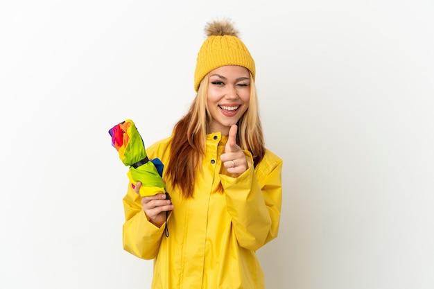 正面を指して笑顔の孤立した白い背景の上に防雨コートを着ている10代のブロンドの女の子