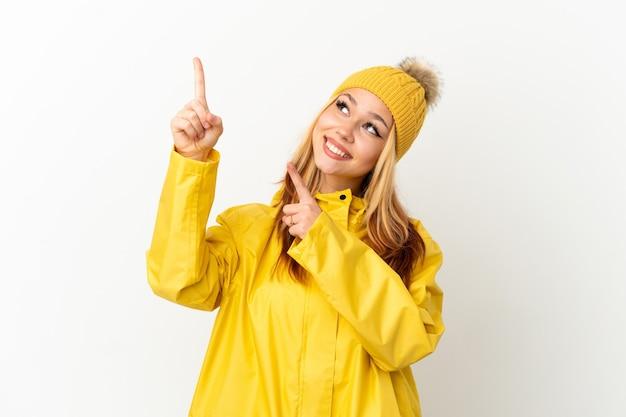 Блондинка-подросток в непромокаемом пальто на изолированном белом фоне, указывая указательным пальцем - отличная идея