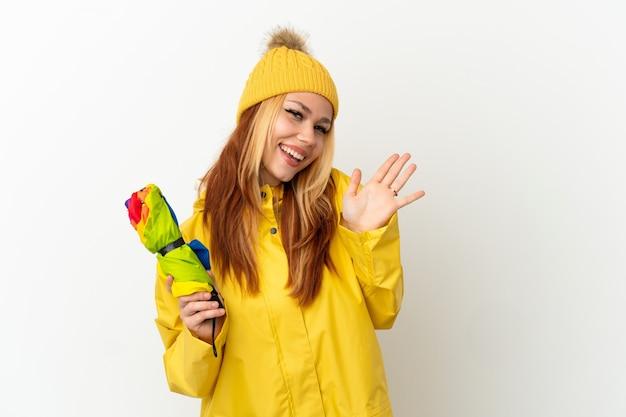 Блондинка девочка-подросток в непромокаемом пальто на изолированном белом фоне салютует рукой с счастливым выражением лица