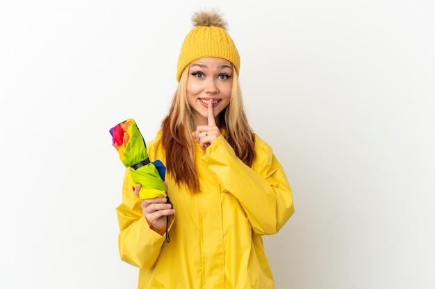 격리된 흰색 배경 위에 방수 코트를 입은 10대 금발 소녀가 입에 손가락을 넣는 침묵 제스처의 표시를 보여줍니다.