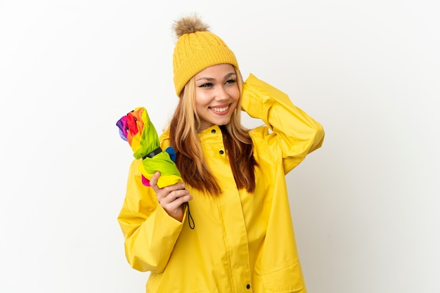 Блондинка девочка-подросток в непромокаемом пальто на изолированном белом фоне думает об идее