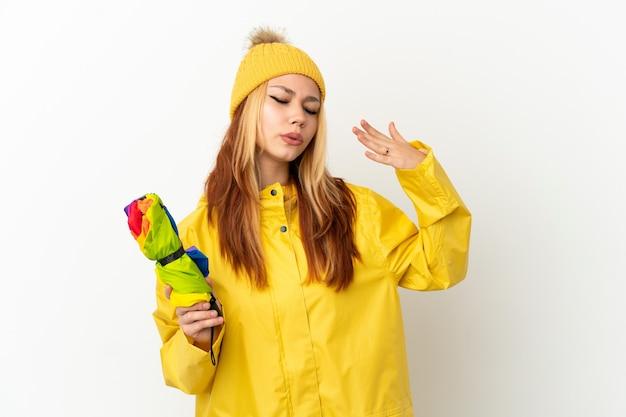 疲れて病気の表情で孤立した白い背景の上に防雨コートを着ているティーンエイジャーのブロンドの女の子
