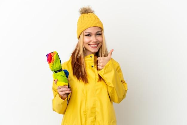 Блондинка девушка-подросток в непромокаемом пальто над изолированной белой стеной показывает палец вверх