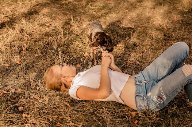 웃으면 서 작은 강아지 발 바리와 큰 안경을 가진 십 대 금발 소녀