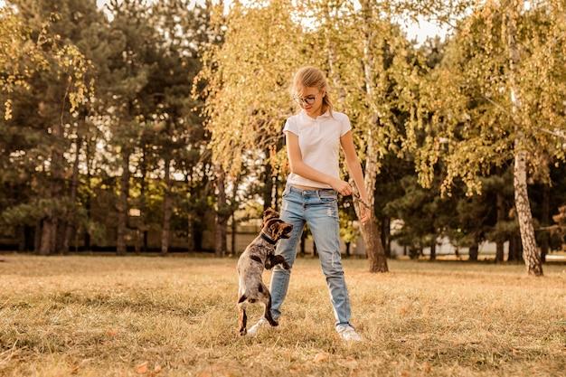 笑って、小さな子犬のスパニエルと遊んで大きなメガネを持つティーンエイジャーのブロンドの女の子