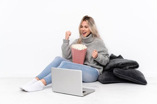 Блондинка подросток ест попкорн во время просмотра фильма на ноутбуке празднует победу