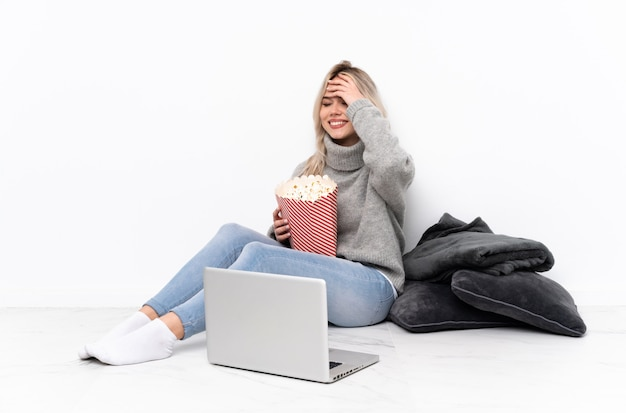 Teenager blonde woman eating popcorn while watching a movie on the laptop smiling a lot