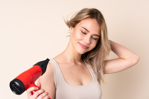 Teenager blonde woman with hairdryer over isolated wall
