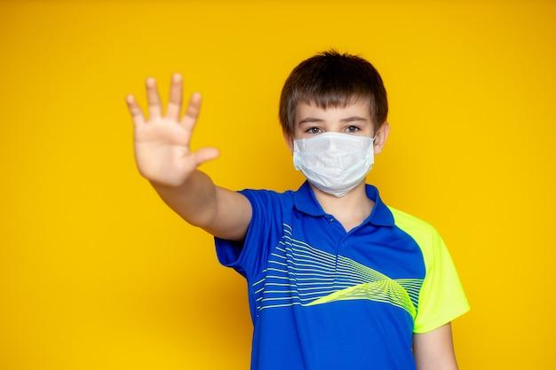 黄色の壁に11〜12歳の少年。ティーンエイジャーは、コロナウイルスとインフルエンザの発生中に顔のマスクを着用しています。ウイルスや病気に対する保護。