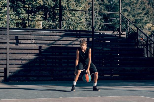 スポーツグラウンドでドリブルするティーンエイジャーの男の子のバスケットボール選手