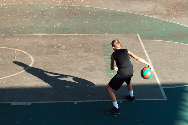 Teenager boy basketball player dribbling on sports ground
