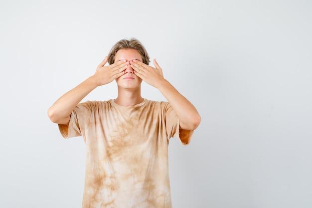 Tシャツを着て両手で目を覆い、怖い顔をしているティーンエイジャーの少年、正面図。