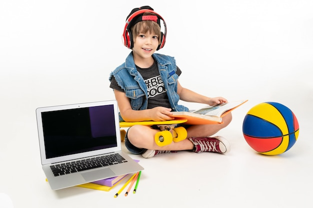 Teenager boy in dark t-shirt, jacket sits with yellow penny, ball, laptop and do homework isolated on white