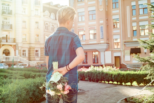 Teenager boy holding bouquet of flowers behind his back.