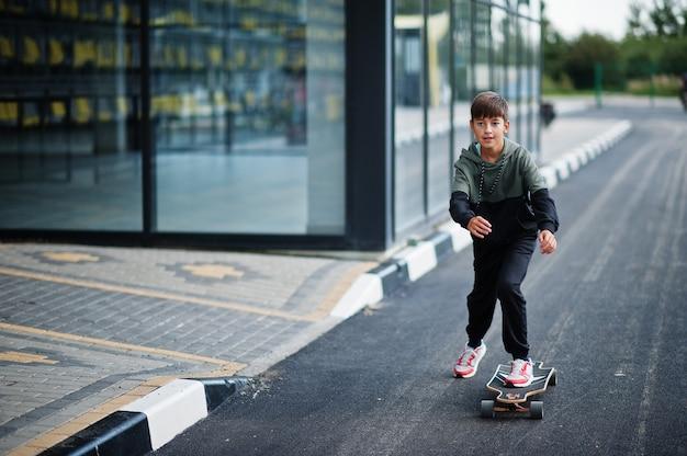 スポーツスーツを着た10代の少年がロングボードに乗る。