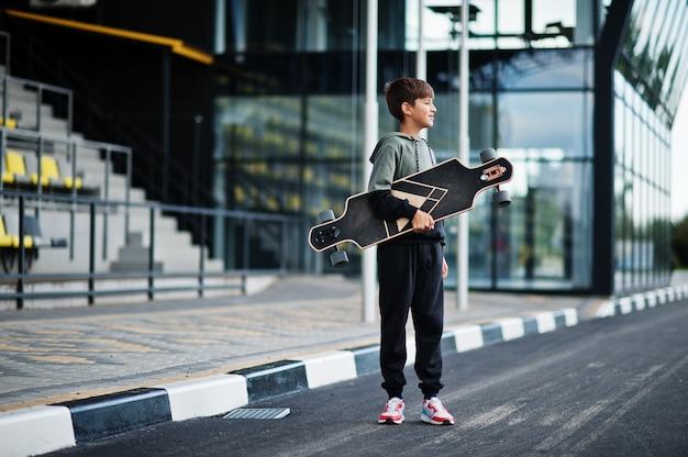 ロングボードでスポーツスーツを着た10代の少年。
