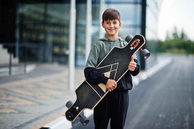 ロングボードでスポーツスーツを着た10代の少年。 Premium写真
