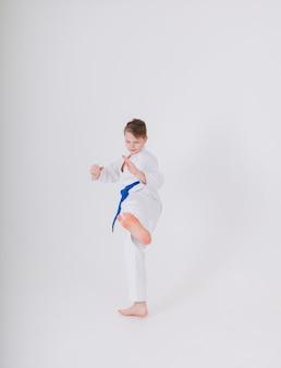 흰 기모노를 입은 십 대 소년이 흰 벽에 킥을 만든다.